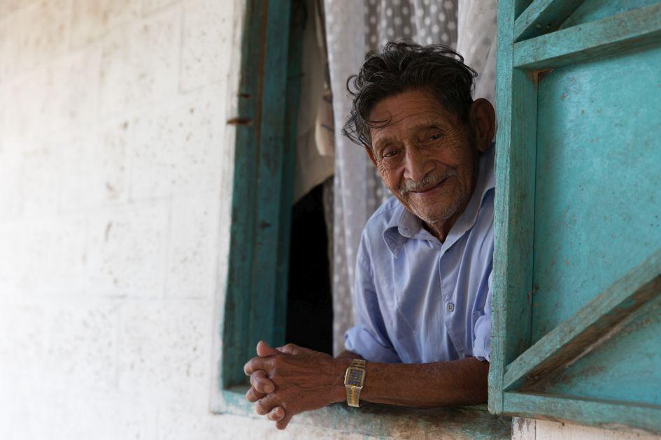 Mann mit Uhr schaut aus dem Fenster und lächelt auf der Finca Hamburgo in Mexiko.